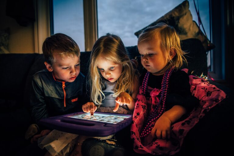 Three children starring at a screen