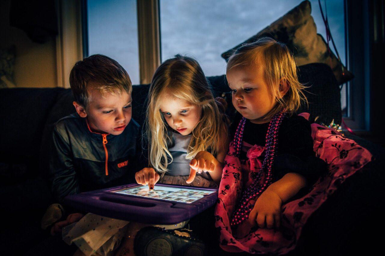Three children starring at a screen