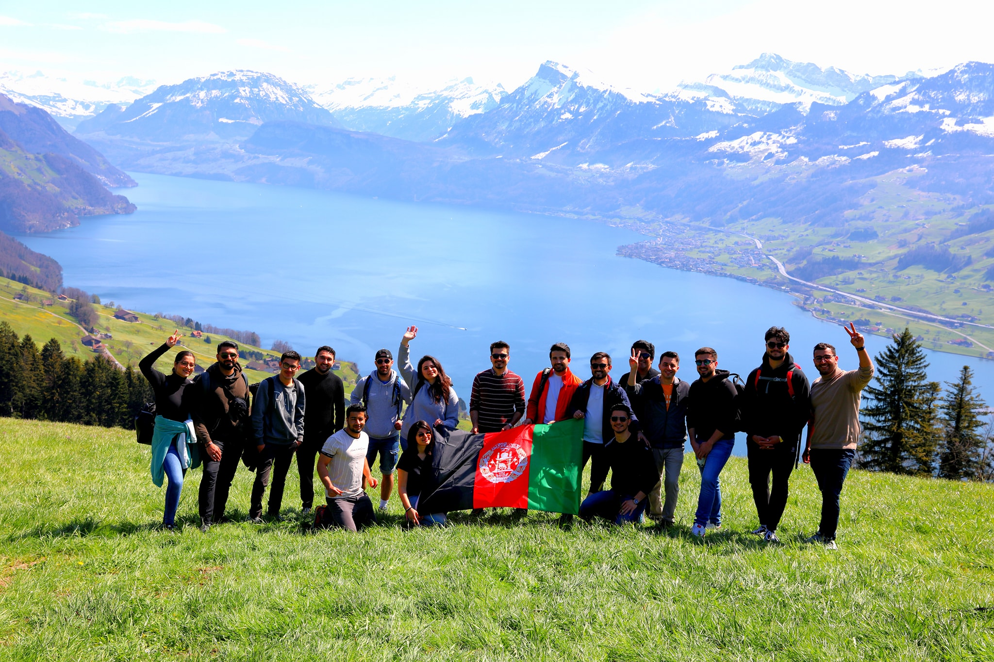 Group of students in front of a lake, holding the afghan flag