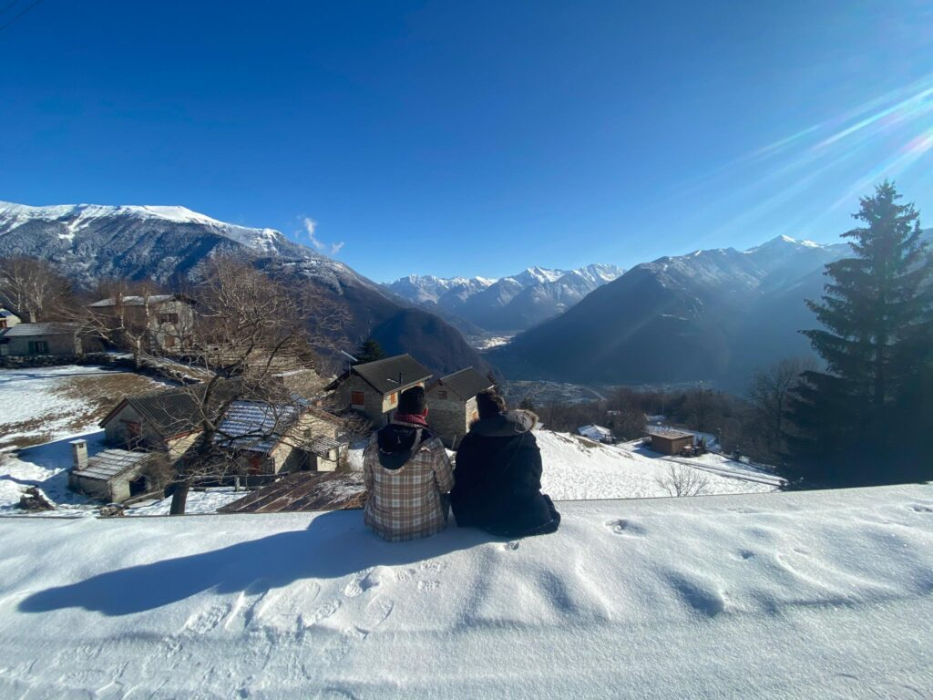 Two friends sitting in the snow looking at the alps