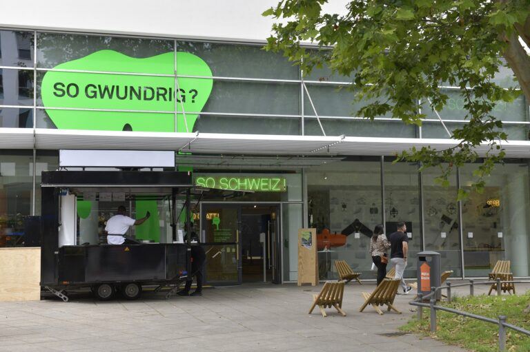 """The entrance of a modern house with a green sign above saying """"so gwundrig"""""""